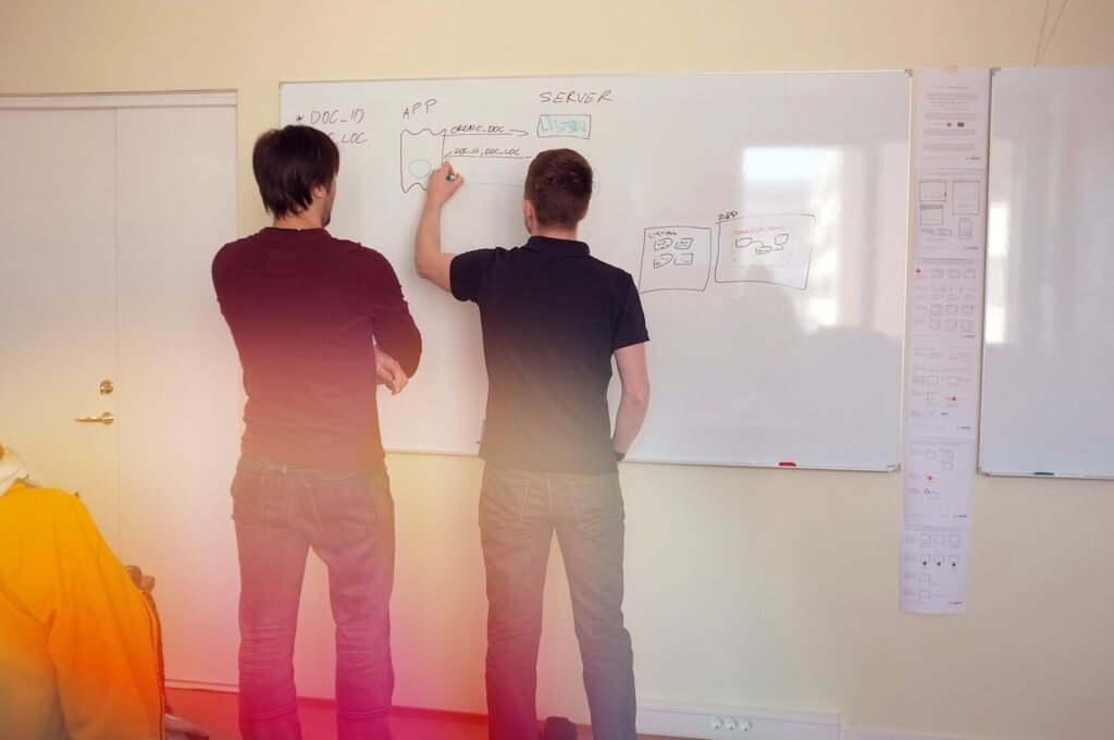 Developers discussing architecture usign whiteboard